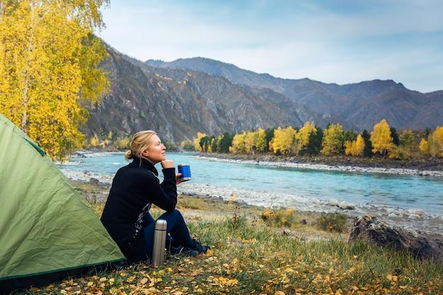 Viaggiatore femminile che si siede sull'erba vicino alla tenda, bevendo caffè dal thermos e ammirando la splendida vista sul fiume e sulle montagne. turista donna del mattino, piacere nel viaggio