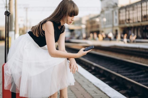 Viaggiatore femminile con il treno in attesa della valigia rossa sulla stazione ferroviaria