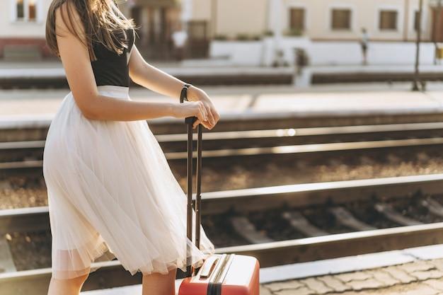 Viaggiatore femminile del brunette con la valigia rossa che cammina sulla stazione raiway