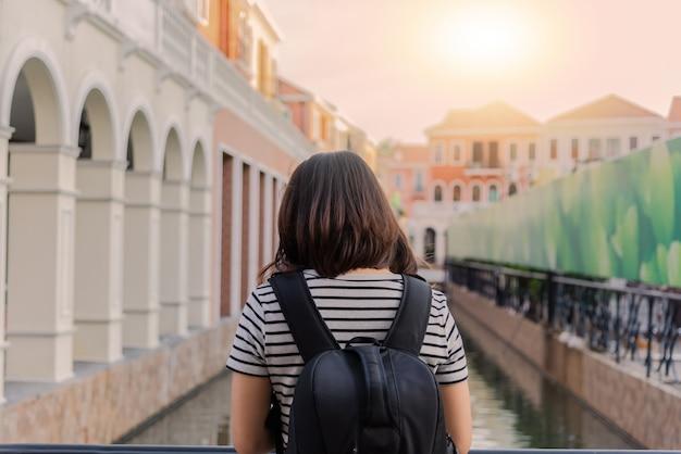 Viaggiatore femminile della giovane asia con lo zaino posteriore e cappello che godono della vista