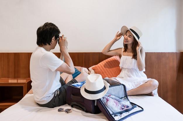 Viaggiatore giovane coppia felice con bagagli in camera d'albergo in vacanza estiva