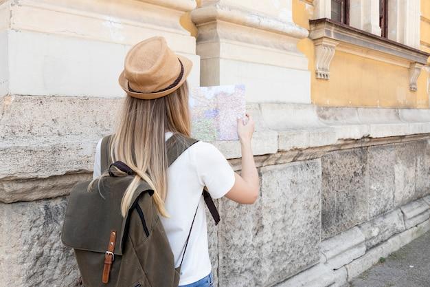 Viaggiatore guardando la mappa da dietro
