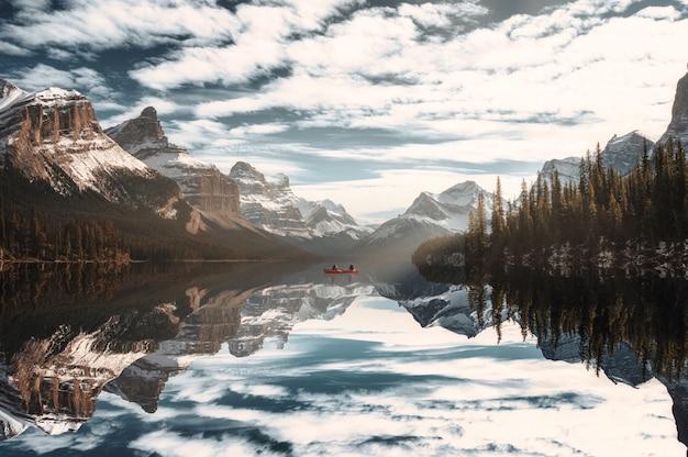 Viaggiatore in canoa nell'isola degli spiriti con le montagne rocciose canadesi sul lago maligne nel parco nazionale di jasper