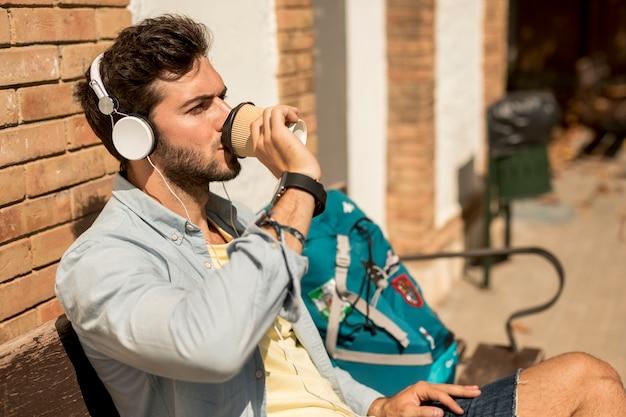 Viaggiatore lateralmente che beve caffè