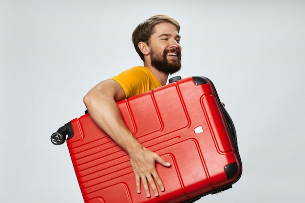 Viaggiatore maschio con una valigia in mano in posa, in vacanza