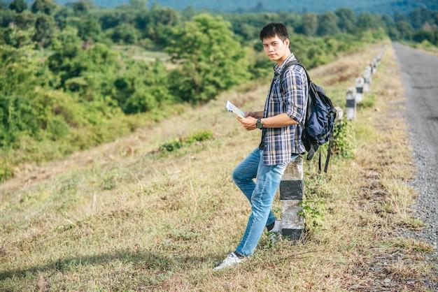 Viaggiatore maschio con uno zaino in possesso di una mappa e in piedi vicino a un chilometro.