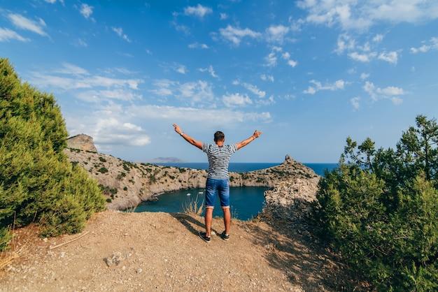 Viaggiatore maschio felice libero con le braccia alzate