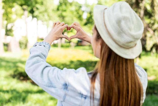 Viaggiatore nel parco che fa una forma di cuore da dietro il colpo