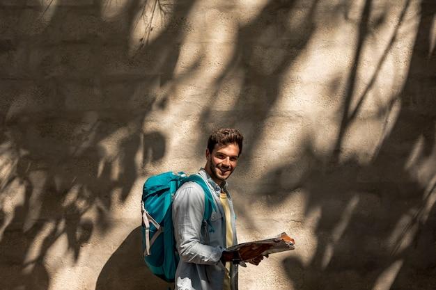 Viaggiatore obliquo che sorride alla macchina fotografica