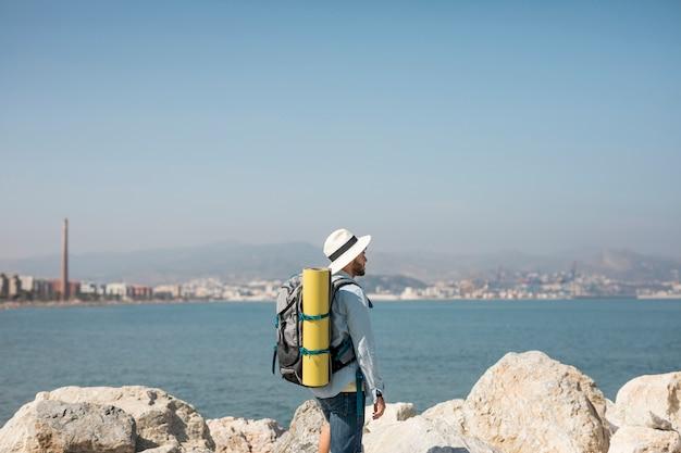 Viaggiatore obliquo in riva al mare