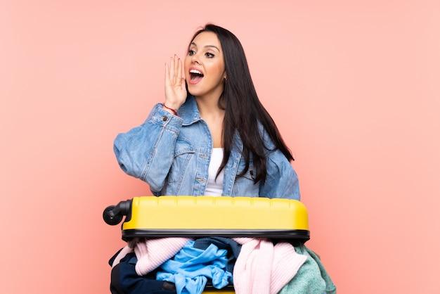 Viaggiatore ragazza colombiana con una valigia piena di vestiti rosa gridando con la bocca spalancata