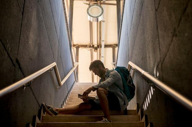 Viaggiatore seduto sulle scale alla stazione ferroviaria