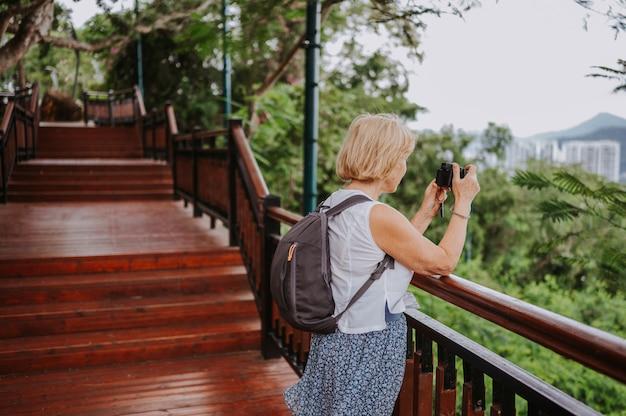 Viaggiatore senior senior con zaino e sacco a pelo donna che cammina prendendo foto nel parco tropicale, viaggi avventura natura in cina, bella destinazione turistica asia, viaggio vacanze estive, spazio copia