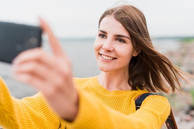 Viaggiatore singolo di smiley che prende un selfie