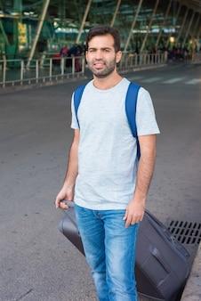Viaggiatore stanco che cammina con la valigia vicino all'aeroporto