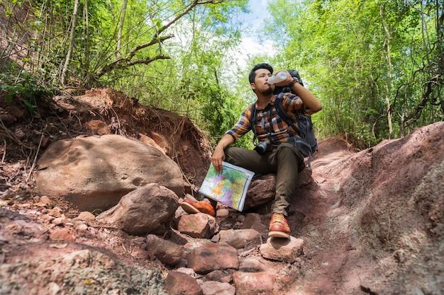Viaggiatore stanco dell'uomo con l'acqua di riposo e dirking dello zaino nella foresta