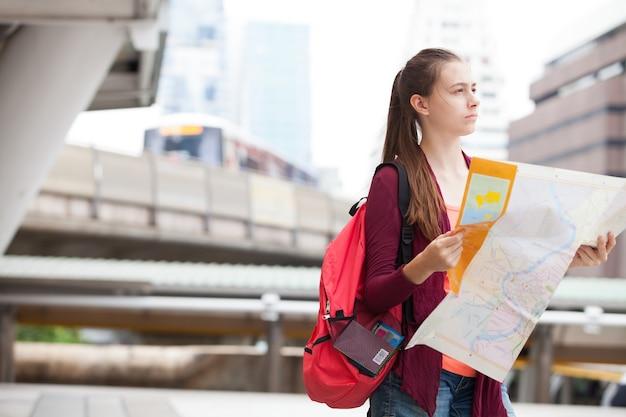 Viaggiatore straniero di bellezza alla ricerca di direzione sulla mappa mentre si viaggia in città