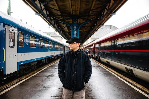 Viaggiatore turistico presso la stazione ferroviaria di budapest in attesa della partenza del suo treno.