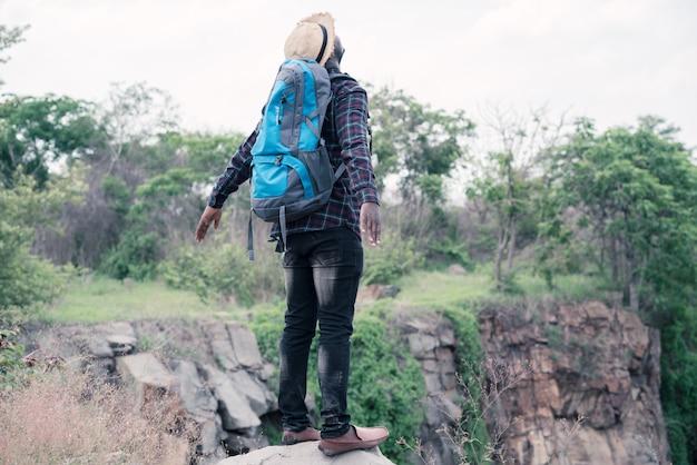 Viaggiatore uomo africano in piedi sulla cima della scogliera e con zaino