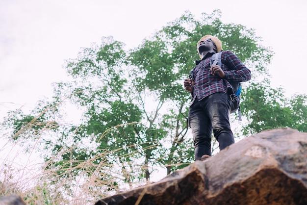 Viaggiatore uomo africano in piedi sulla cima di moutain e con zaino