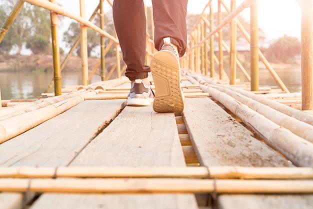 Viaggiatore uomo che cammina verso il successo sul lungo ponte di bambù in legno