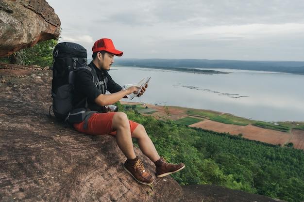 Viaggiatore uomo con zaino guardando la mappa sul bordo della scogliera, sulla cima di una montagna di roccia