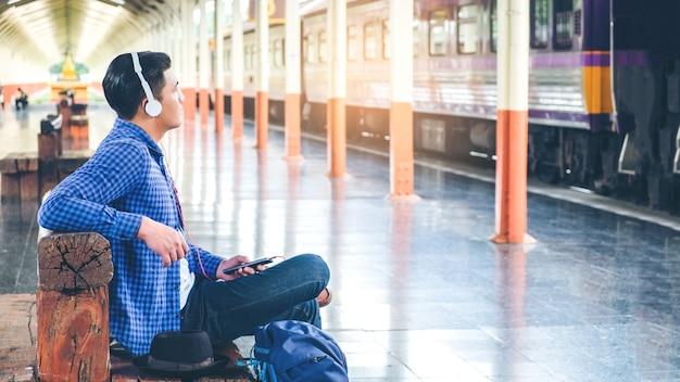 Viaggiatore uomo utilizzando tablet e cuffie in attesa del treno sulla stazione