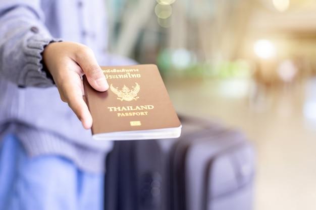 Viaggiatori che mostrano il loro passaporto della tailandia all'aeroporto