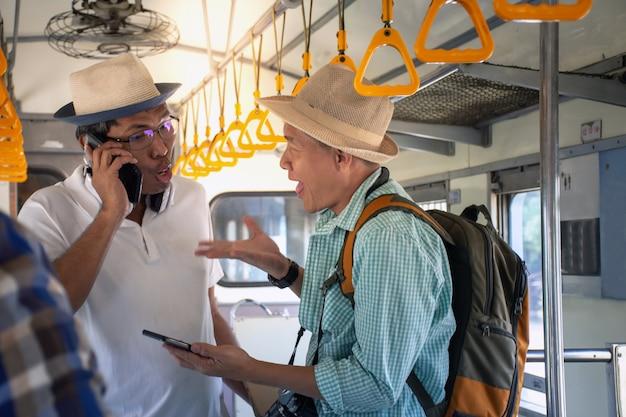 Viaggiatori con zaino e sacco a pelo asiatici arrabbiati che hanno un problema e che discutono viaggiano in treno in vacanza