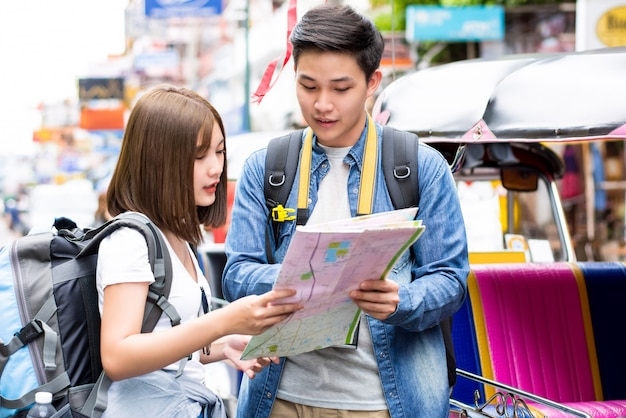 Viaggiatori con zaino e sacco a pelo turistici asiatici delle coppie che viaggiano in strada bangkok tailandia di khao san