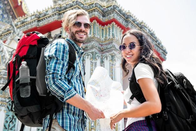 Viaggiatori con zaino e sacco a pelo turistici che viaggiano in tempio tailandese antico in vacanza in tailandia