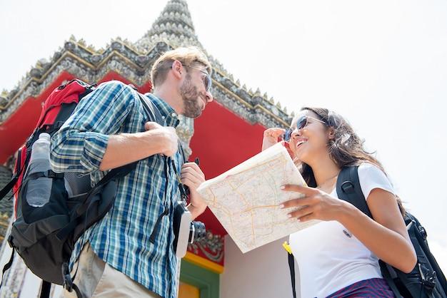 Viaggiatori con zaino e sacco a pelo turistici che viaggiano in tempio tailandese antico sulle vacanze in tailandia