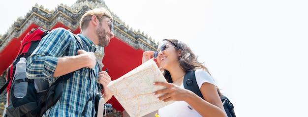 Viaggiatori con zaino e sacco a pelo turistici delle coppie che viaggiano in tempio tailandese sulle vacanze estive a bangkok