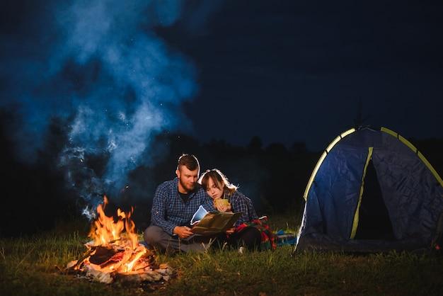 Viaggiatori di coppia felice seduti insieme accanto al fuoco e tenda turistica incandescente