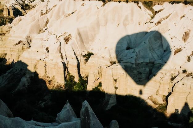 Viaggiatori e turisti che sorvolano le montagne al tramonto in un pallone aerostato colorato a goreme.