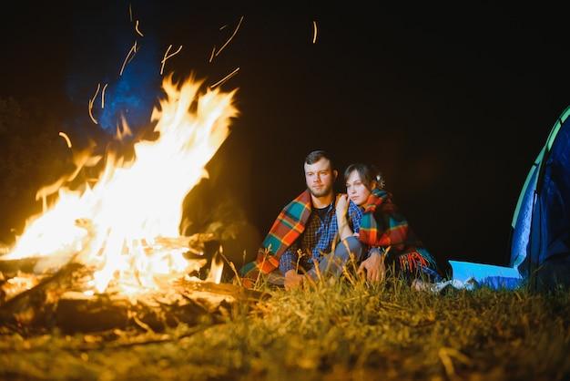 Viaggiatori felici delle coppie romantiche che riposa al falò vicino alla tenda turistica luminosa sotto il cielo notturno incredibile