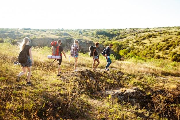 Viaggiatori giovani giovani amici con zaini a piedi nel canyon