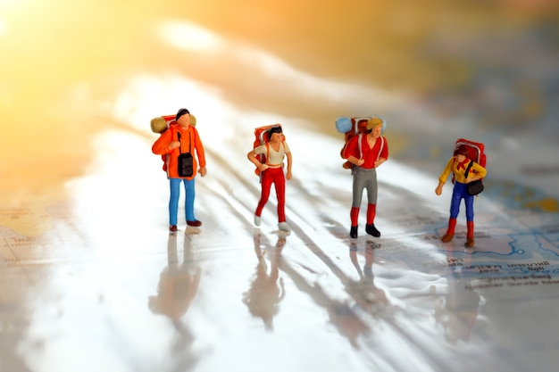 Viaggiatori in miniatura con zaino in piedi sulla mappa, viaggi e concetto di avventura.