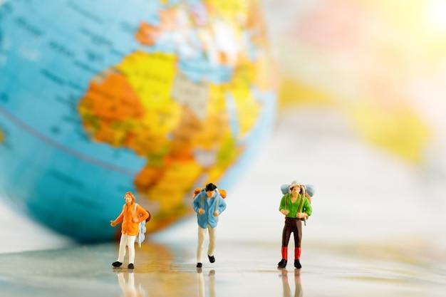 Viaggiatori in miniatura e zaino su mappa e globo, concetto di viaggio intorno al mondo e avventura.