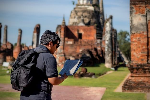 Viaggiatori uomini asiatici in cerca di mappa in un tempio phar sri sanphet ayutthaya.