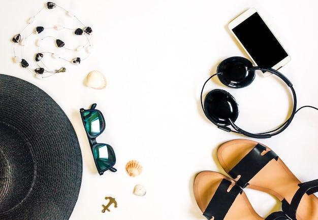 Viaggio accessori femminili telefono, auricolari, occhiali da sole, sandali, collana e cappello su bianco.