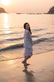 Viaggio andante della donna felice sulla spiaggia di sabbia tropicale di estate