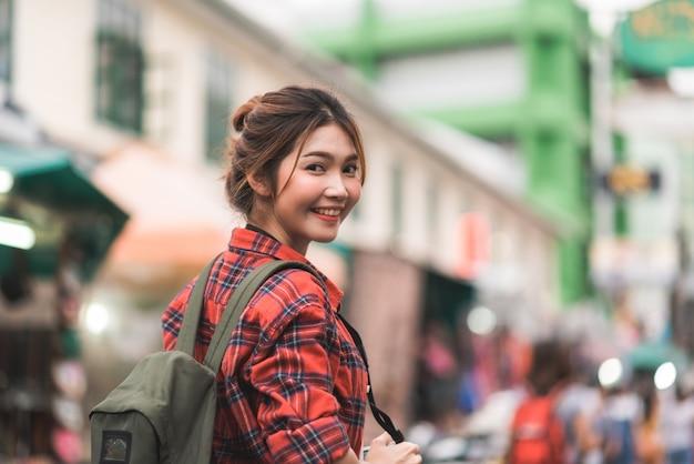 Viaggio asiatico della donna di viaggiatore con zaino e sacco a pelo del viaggiatore in strada di khao san a bangkok, tailandia