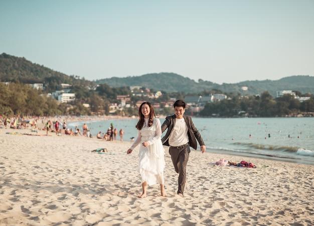 Viaggio di luna di miele andante delle coppie felici sulla spiaggia di sabbia tropicale