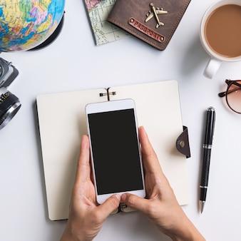 Viaggio di vacanza di pianificazione del giovane viaggiatore e cercare informazioni o prenotare hotel sul computer portatile e sullo smartphone, concetto di viaggio