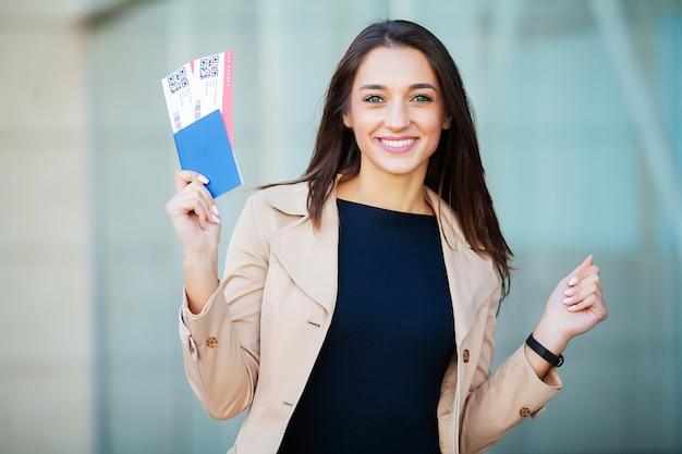 Viaggio. donna che tiene due biglietti aerei nel passaporto all'estero vicino all'aeroporto