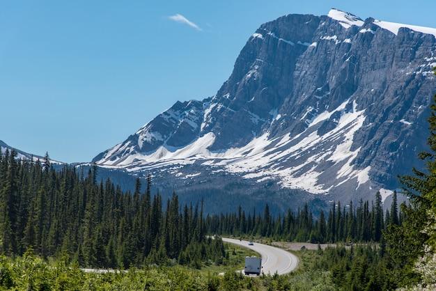 Viaggio stradale con una grande vista di grande montagna e cielo blu in alberta, canada