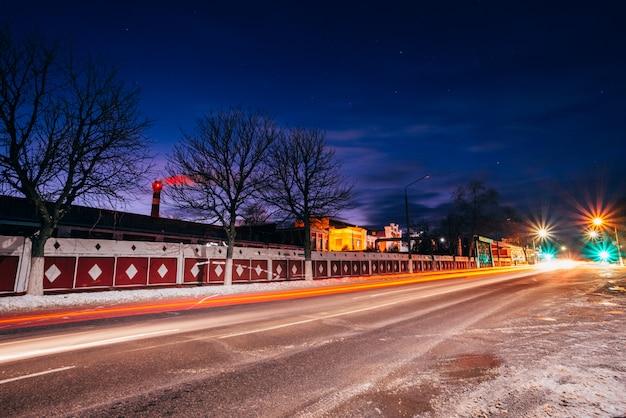 Viale della città di notte sullo sfondo della fabbrica