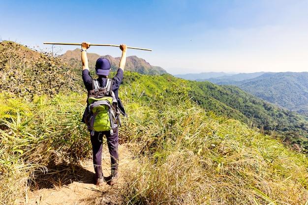 Viandante che alza le armi e che tiene bastone di legno nella cima di una montagna