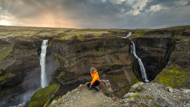 Viandante che esamina le grandi cascate in islanda al tramonto